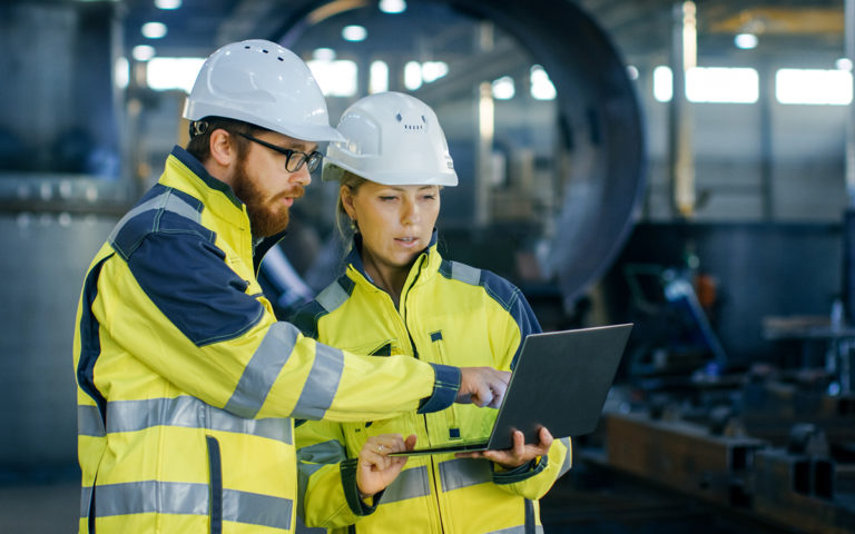 Male and Female Industrial Engineers in Hard Hats Discuss New Project while Using Laptop