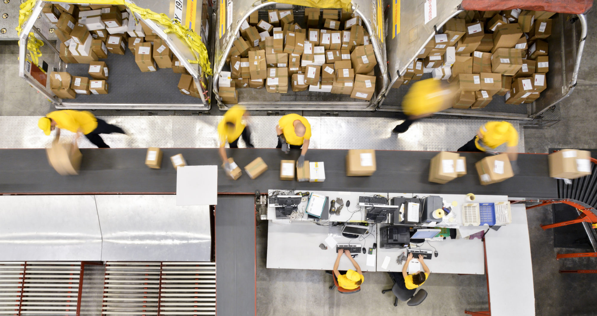Workers processing boxes on conveyor belt in distribution warehouse,