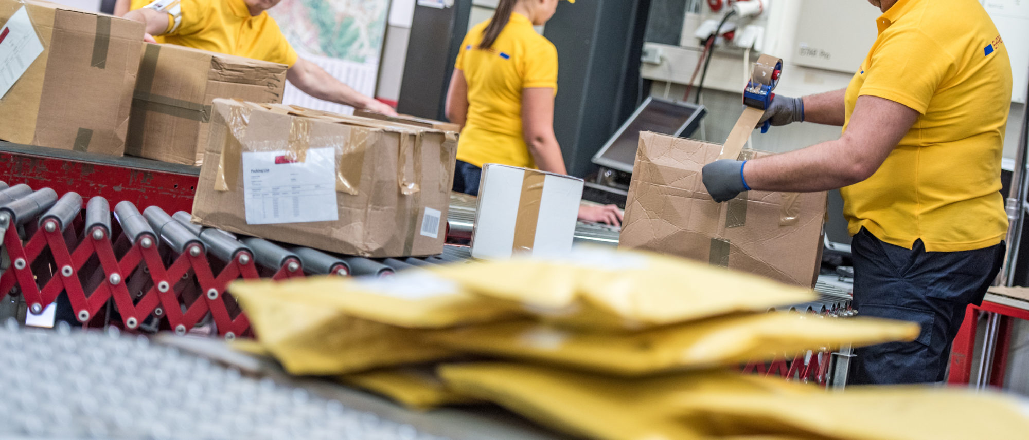 Group of postal workers in yellow uniforms handling boxes on a conveyor belt in a warehouse.