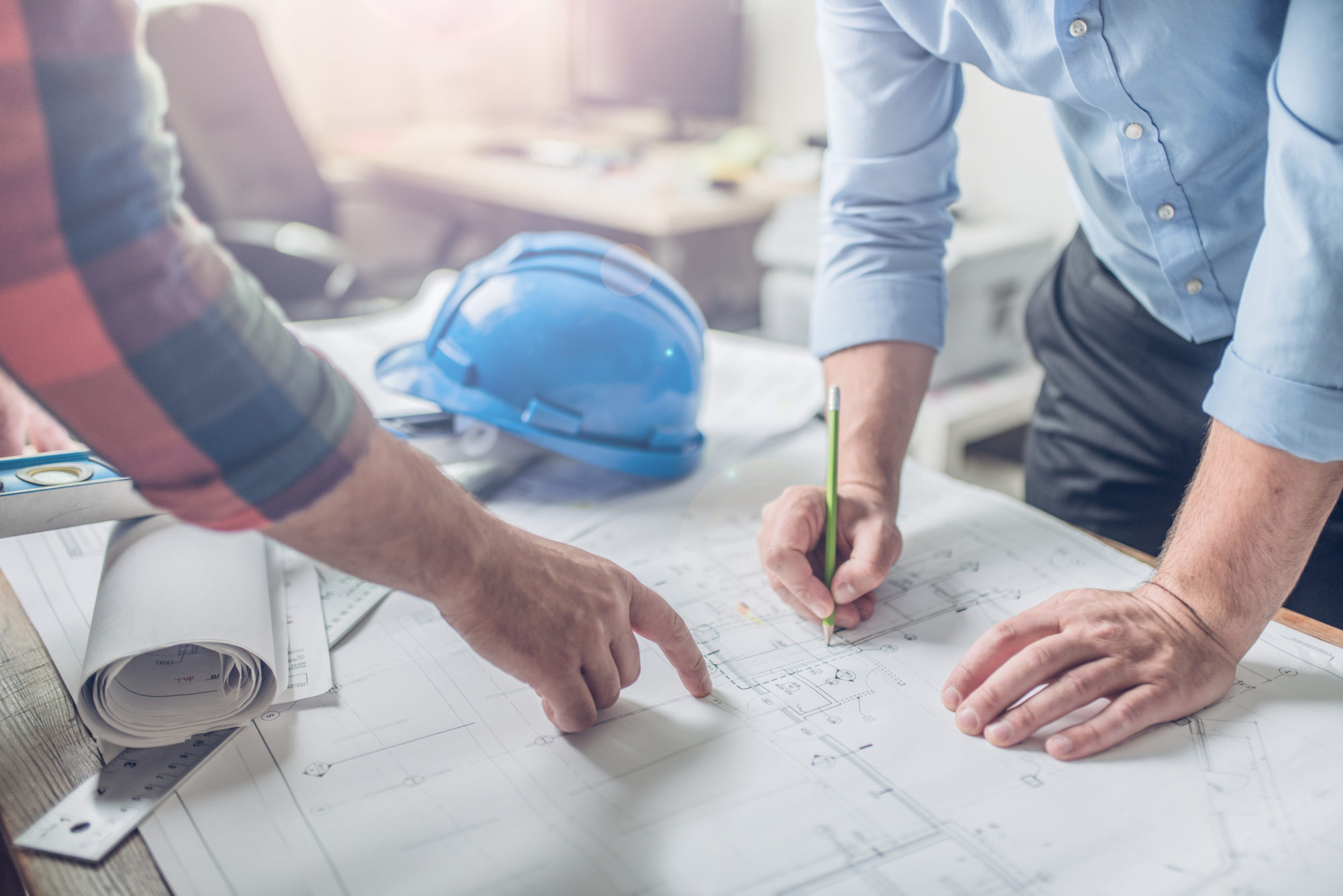 Hands of an architect and an engineer pointing at the architectural plan