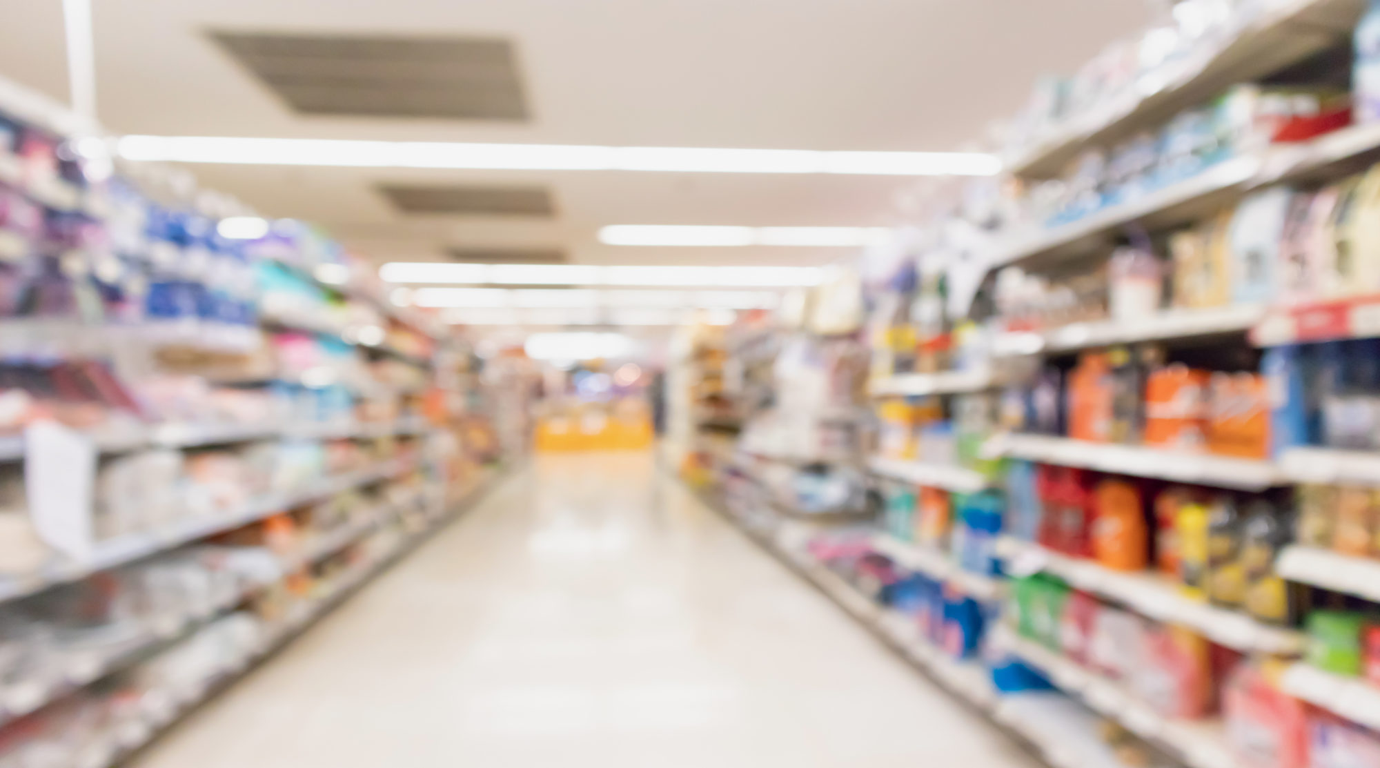 Supermarket aisle with product on shelves blurred background